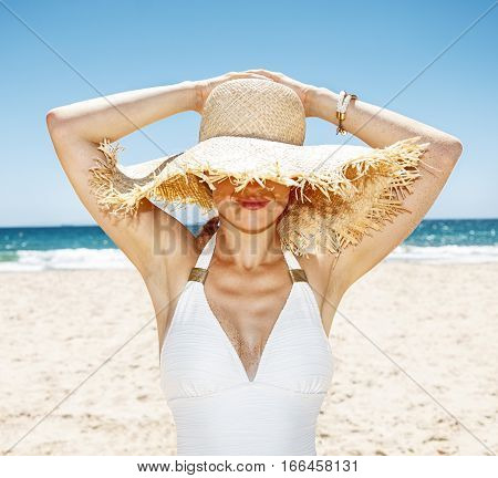 Smiling Woman In Swimsuit Hiding Under Big Straw Hat At Beach