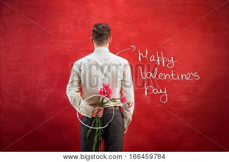Man holding bouquet of carnations behind back on red studio background. The happy Valentine's Day concept