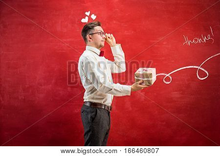 Young funny man with gift on red studio background. The happy Valentine's Day concept
