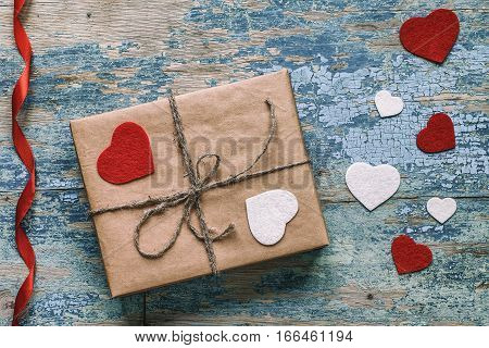 Gift box with hearts on wooden background with crackling effect. Happy valentine's day idea