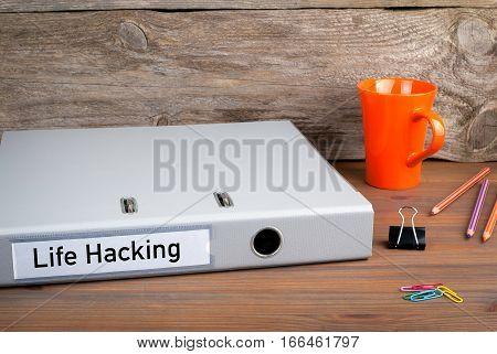 Life Hacking. Folder, Coffee Mug on wooden office desk.