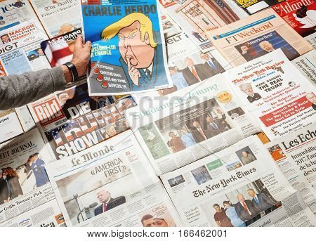 PARIS FRANCE - JAN 21 2017: Man holding Die Welt above major international newspaper journalism featuring headlines with Donald Trump Barack Obama Melania Trump and Michele Obama inauguration as the 45th President of the United States in Washington D.C