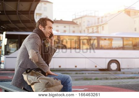Man waiting at the bus station and talking on the mobile phone