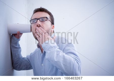 Man spying and listening a discussion on the wall