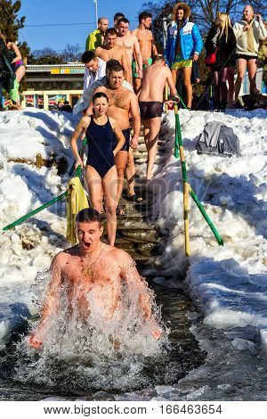 Uzhgorod Ukraine - January 19 2017: Greek-Catholic parishioners by orthodox tradition dip in the icy river during the Epiphany celebration. Epiphany Day completes the Christmas-New Year festivities cycle in Ukraine.