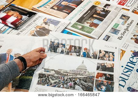 PARIS FRANCE - JAN 21 2017: Man holding Die Welt above major international newspaper journalism featuring headlines with Donald Trump inauguration as the 45th President of the United States in Washington D.C