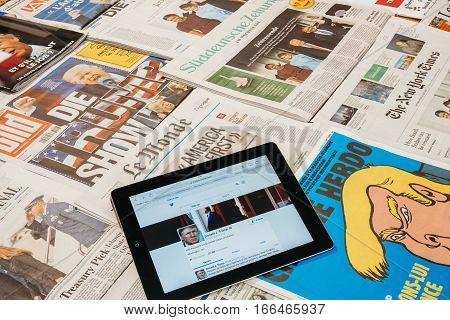 PARIS FRANCE - JAN 21 2017: iPad to twitter account of Donald Trump above major international newspaper journalism featuring headlines with Donald Trump inauguration as the 45th President of the United States in Washington D.C