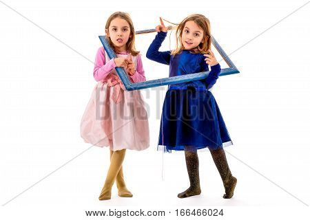 Twin Girls Are Making Happy Expressions With Picture Frame.
