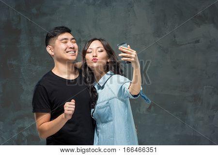 Portrait of smiling Korean couple making selfie photo on a gray studio background
