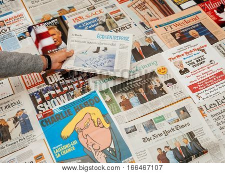PARIS FRANCE - JAN 21 2017: Man holding Le Mode above major international newspaper journalism featuring headlines Davos Forum and inauguration as the 45th President of the United States in Washington D.C