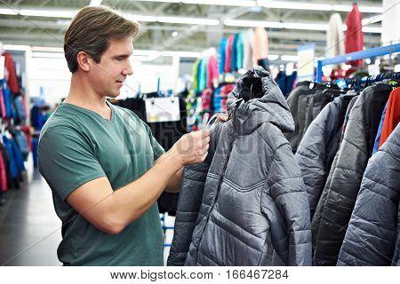 Man Chooses Winter Jacket In Store