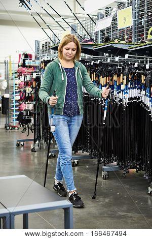 Woman Chooses Nordic Walking Poles In Store