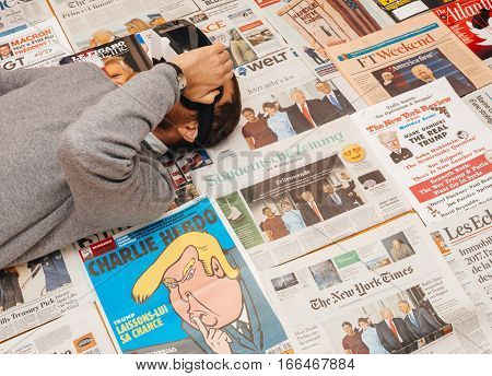 PARIS FRANCE - JAN 21 2017: Man wearing VR Virtul Reality map above major international newspaper journalism featuring headlines with Donald Trump inauguration as the 45th President of the United States in Washington D.C