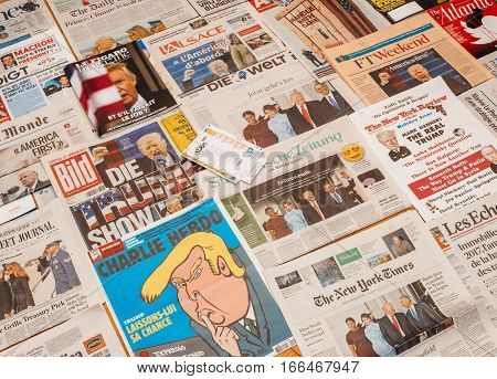 PARIS FRANCE - JAN 21 2017: Lottery ticket above major international newspaper journalism featuring headlines with Donald Trump inauguration as the 45th President of the United States in Washington D.C