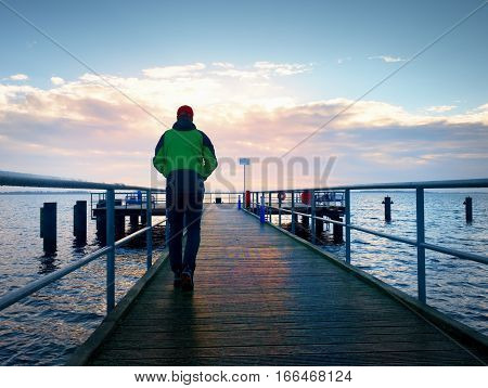 Adult Tall Man On Pier Board Look Over Sea To Morning Sun. Smooth Water Level