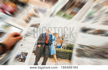 PARIS FRANCE - JAN 21 2017: Man holding Die Welt above major international newspaper journalism featuring headlines with Donald Trump and Melania Trump inauguration as the 45th President of the United States in Washington D.C