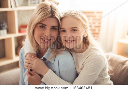 Cute teenage girl and her beautiful mom are hugging looking at camera and smiling while sitting on sofa at home