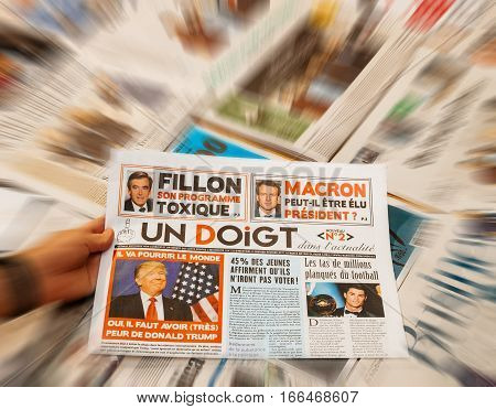 PARIS FRANCE - JAN 21 2017: Un Doigt - One Finger magazine above major international newspaper journalism featuring portrait of Donald Trump inauguration as the 45th President of the United States in Washington D.C