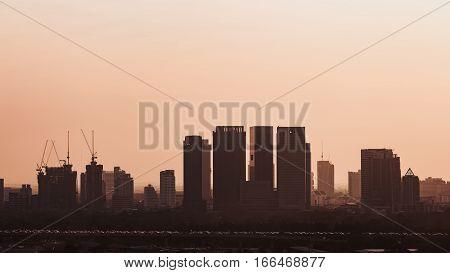 Silhouette scene of buildings and traffic inside Bangkok Thailand in morning having orange tone sky as background from sunlight.