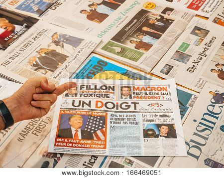 PARIS FRANCE - JAN 21 2017: Un Doigt - One Finger magazine above major international newspaper journalism and middle finger featuring portrait of Donald Trump inauguration as the 45th President of the United States in Washington D.C