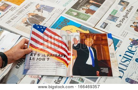 PARIS FRANCE - JAN 21 2017: Man reading holding Le Figaro above major international newspaper journalism featuring portrait of Donald Trump inauguration as the 45th President of the United States in Washington D.C