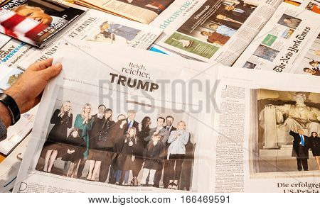 PARIS FRANCE - JAN 21 2017: Man holding Die Welt above major international newspaper journalism featuring headlines with Donald Trump family at inauguration as the 45th President of the United States in Washington D.C