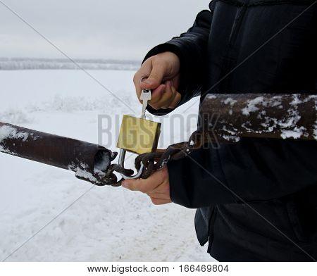 Man opening gold padlock on metal old gates at winter