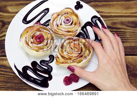 woman's hand take one of three apple muffins drizzled with chocolate sauce leaving a zigzag trail on a white plate on a wooden brown background