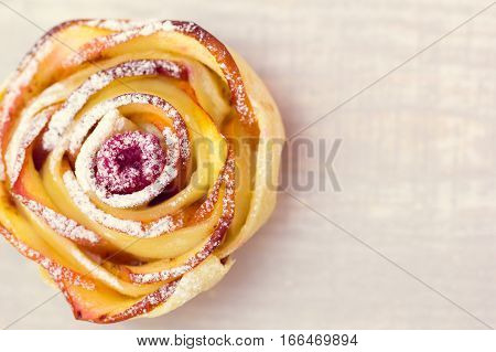 apple muffin with raspberry in the centre on a wooden light background