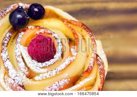 apple muffin with raspberry and blueberries on a striped wooden background
