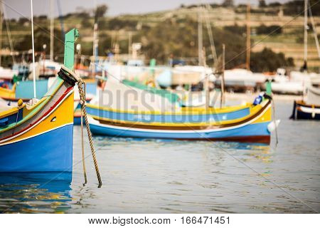A view across Marsaxlokk harbor dominated by traditional Maltese fishing boats Luzzu decorated in their familiar bright colors and eyes painted on the bows.