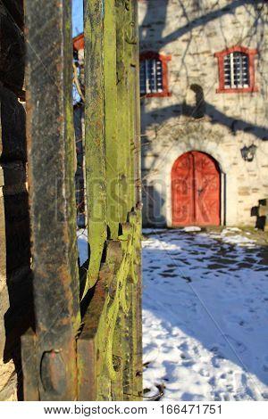 Verwittertes antikes Eisentor im Hintergrund die Denkmalgeschützte Pfarrkirche St.Thomas. Romanischer Kernbau 12 Jh. ,renouviert 1764 und1935