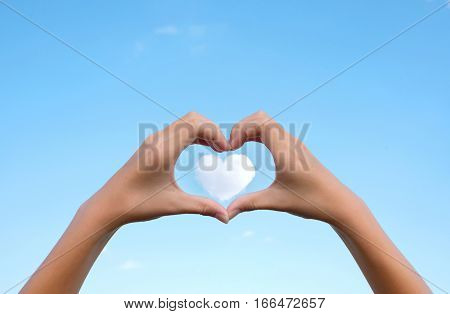 Asian young girl hands holding hands in heart shape framing on cloud heart shape with clear blue sky background for Happy valentines day or wedding concept and copy space.