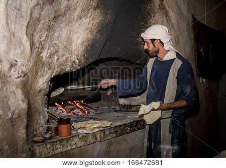 NAZARETH ISRAEL - DECEMBER 16: Man dressed in period clothes bakes bread in Nazareth Village Israel on December 16 2016