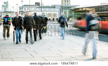 Abstract long exposure with bleached processing of London office workers and commuters on London Bridge during a cold winters day.