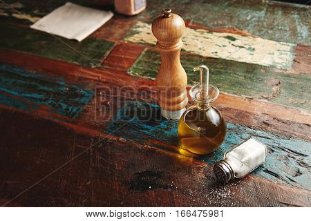 Wooden pepper grinder next to small glass dispencer with virgin extra olive oil inside stands near lying vitage jar with white sea salt, all isolated on distressed wooden table, top view