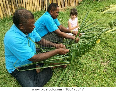 Fijian men teach young tourist girl how to create a basket from weaving a Coconut Palm leaves.Travel Fiji concept Real people copy space poster