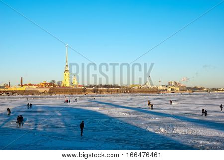 SAINT-PETERSBURG, RUSSIA, JANUARY 21, 2017: People walk on the Neva River ice near The Old Saint Petersburg Stock Exchange and Rostral Columns. On the background is Saints Peter and Paul Fortress