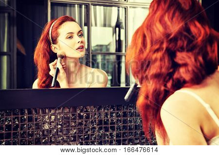 Red-haired Girl Looking In The Mirror And Applying Cosmetic With