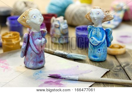 Paintbrush paint in jars and handmade figurines