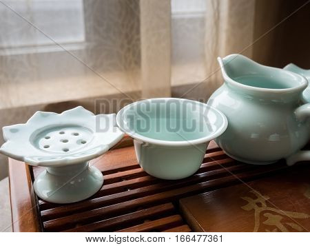 Modern turquoise ceramic Chinese tea set - closeup of tea bag rester, strainer and jug on a traditional wooden tray. The rester is shaped in a lotus flower design. The partial Chinese character means