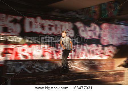 Young man rollerblading. Rollerblader near graffiti. Not afraid of speed.