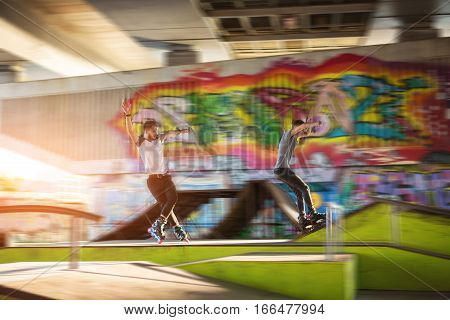 Young men rollerblading. Rollerbladers near graffiti. Faster and faster.