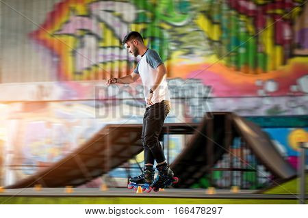 Young male rollerblading. Person near graffiti. Speed and precision of moves.