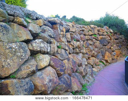 Retaining wall from rough granite blocks in residential street in Alora Andalucia