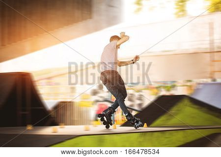 Man is rollerblading. Slalom cones and rollerblader. Improve your balance.