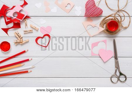 Valentines day holiday scrapbooking frame background, wedding decorations. Handmade gift greeting card creating, cut and paste, craft paper, felt and diy tools on white wood. Above view, flat lay