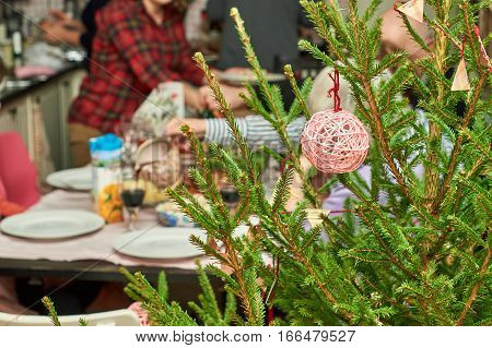 Decorated Christmas tree on foreground with family at festive table on the background