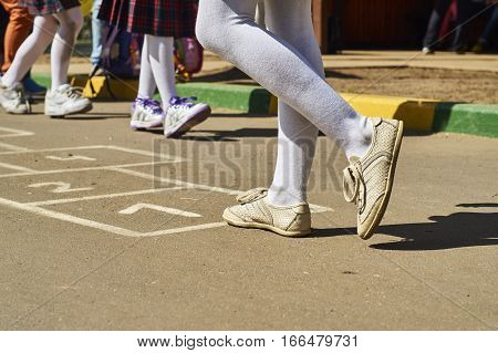 Little schoolgirls playing hopscotch after lessons on schoolyard