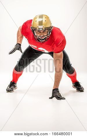 American football player in protective sportswear looking at camera on grey